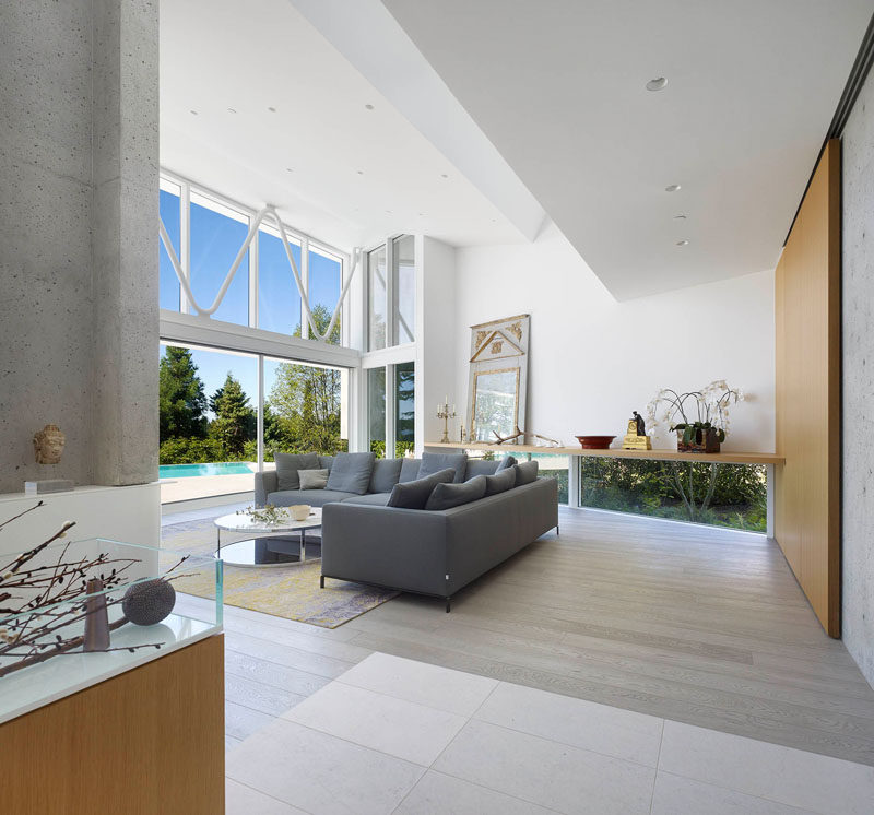 This living room, with double-height ceilings, opens up to the deck and swimming pool. Small windows located at the bottom of the wall, run along the length of the room