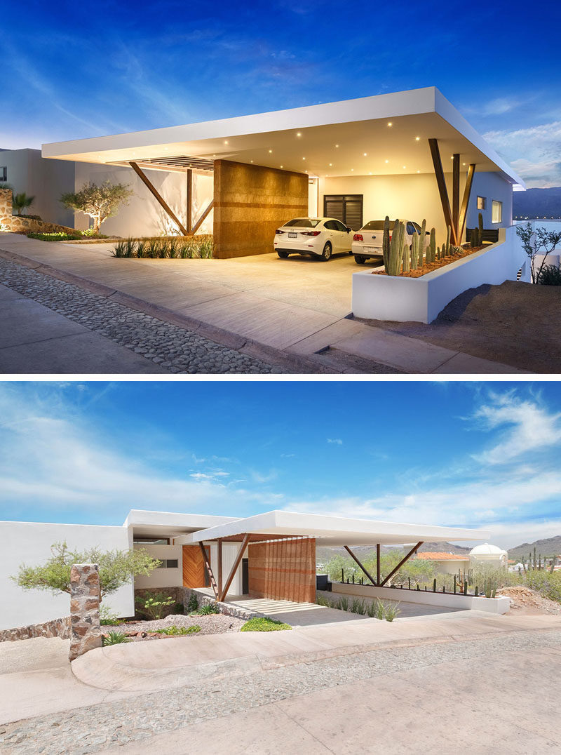 This home has a covered carport with a rammed earth feature wall, that is also brightly lit at night.
