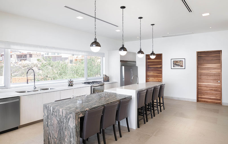 This kitchen has a large window running the length of the counter, and a dual-height island, providing plenty of space for meals and entertaining.