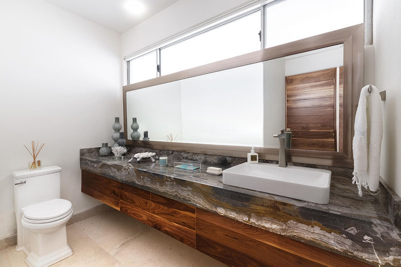 In this bathroom, a single long mirror and windows, both run the length of the vanity.