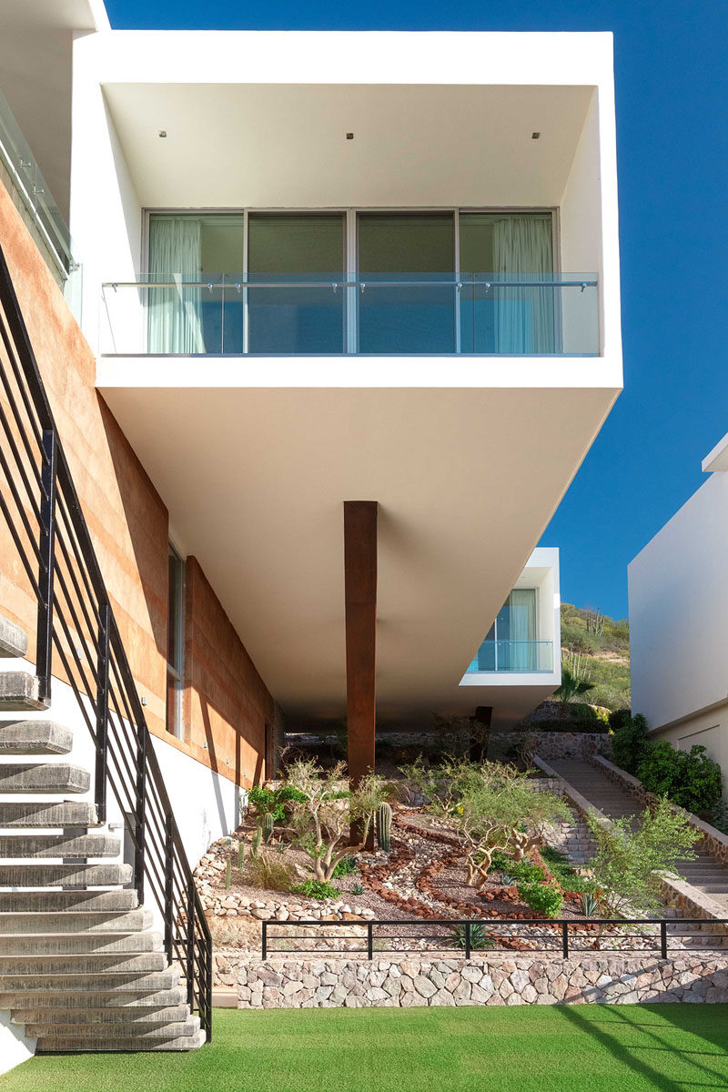 Creative landscaping has been used to liven up a void under this overhanging section of a house.