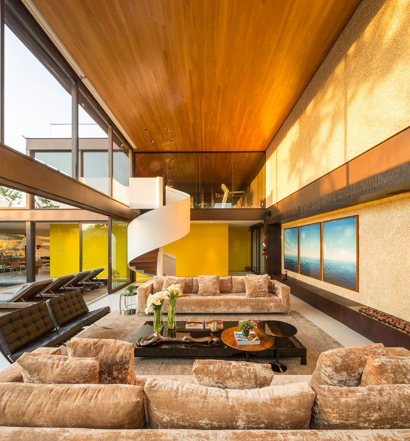 This large living area has a double-height ceiling, a bright yellow feature wall and a wooden ceiling.