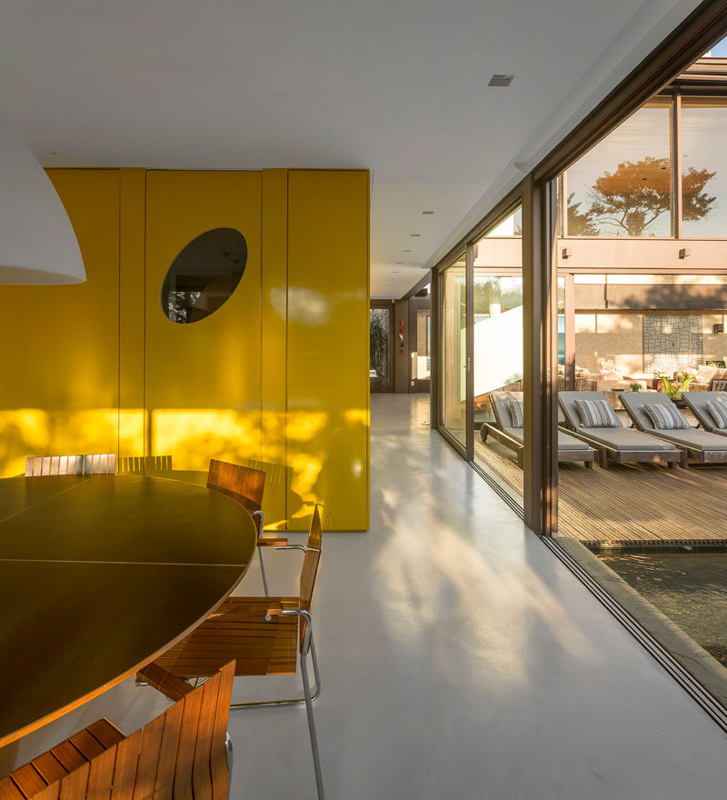 This Brazilian home has a bright yellow feature wall that hides the guest bathroom, kitchen, pantry and service stairs.