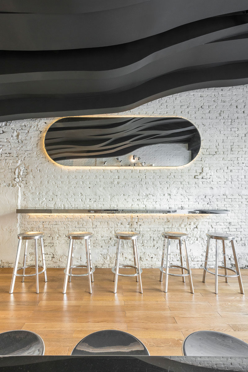 Bar seating and a mirror runs along the wall in this cafe. Both have hidden lighting.