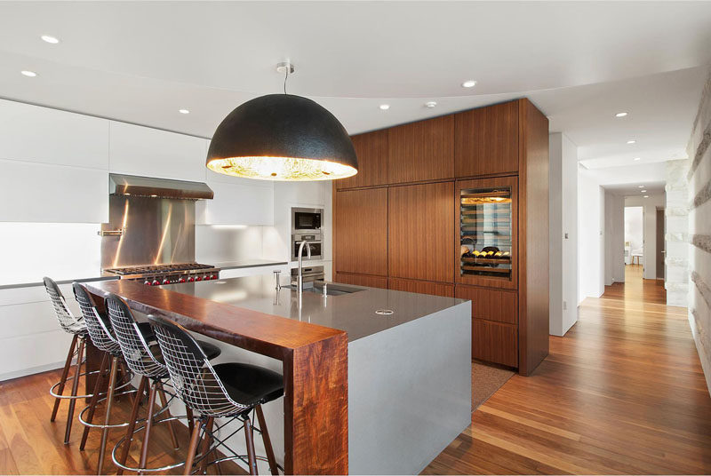 In this kitchen, there's a central island with bar seating and a large pendant light.