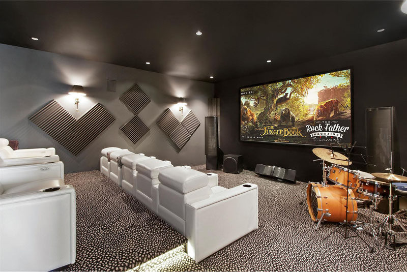 This home theater room has tiered white lounge chairs, perfect for movie viewing.