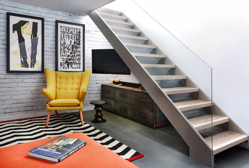 This TV/living room features an open tread glass and steel staircase.