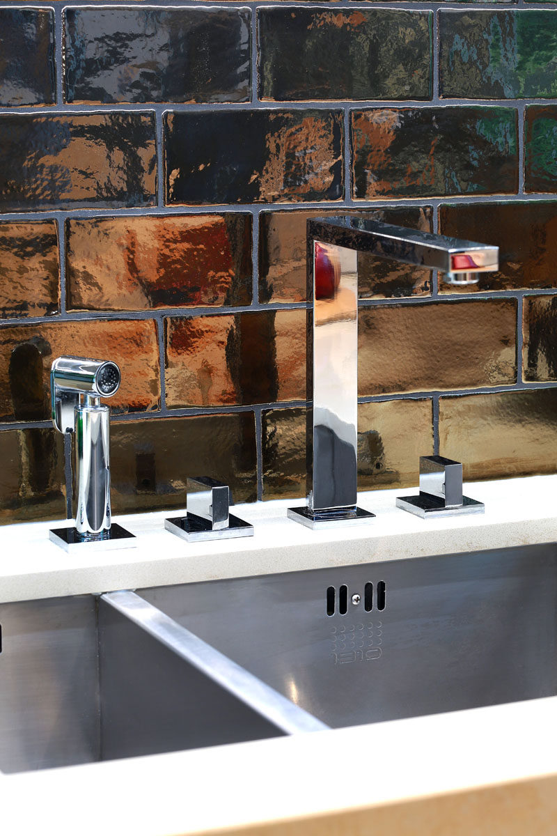 A stainless steel undermount sink and faucet, and dramatic dark bronze tiles have been used in the design of this kitchen.