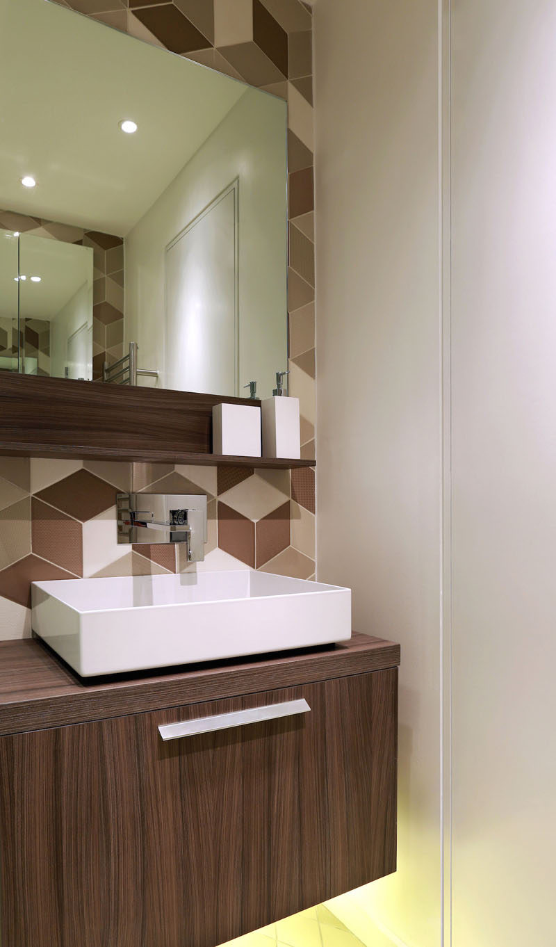 This shower room, has a huge shower and statement tiles in a diamond shape in tones of cream, cappuccino and chocolate. An LED under-lit wooden vanity unit and mirror finish the look.