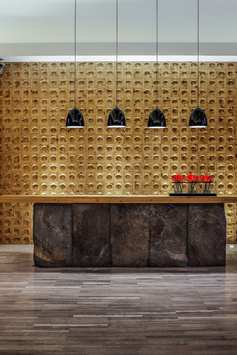 This spa reception area has a large desk, with the dark stone contrasting the wooden feature wall.