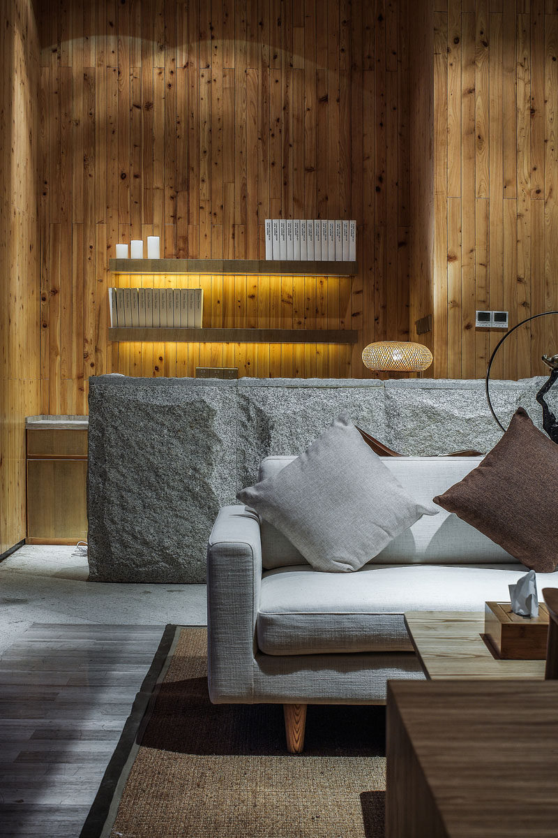 A lighter colored stone has been used as a feature material in this lounge area of a spa, and smaller design elements, like hidden lighting under the floating shelves have also been included.