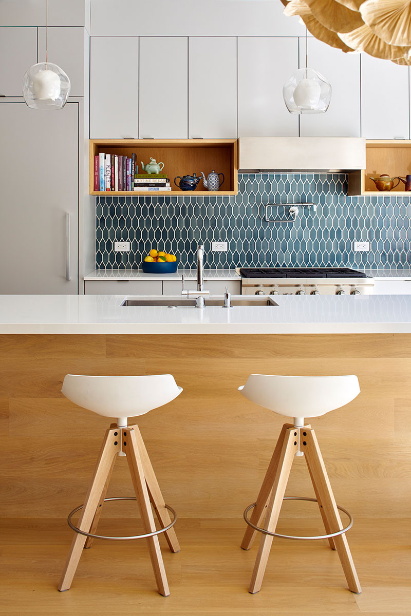 Blue tiles add some color to this white and wood kitchen palette.