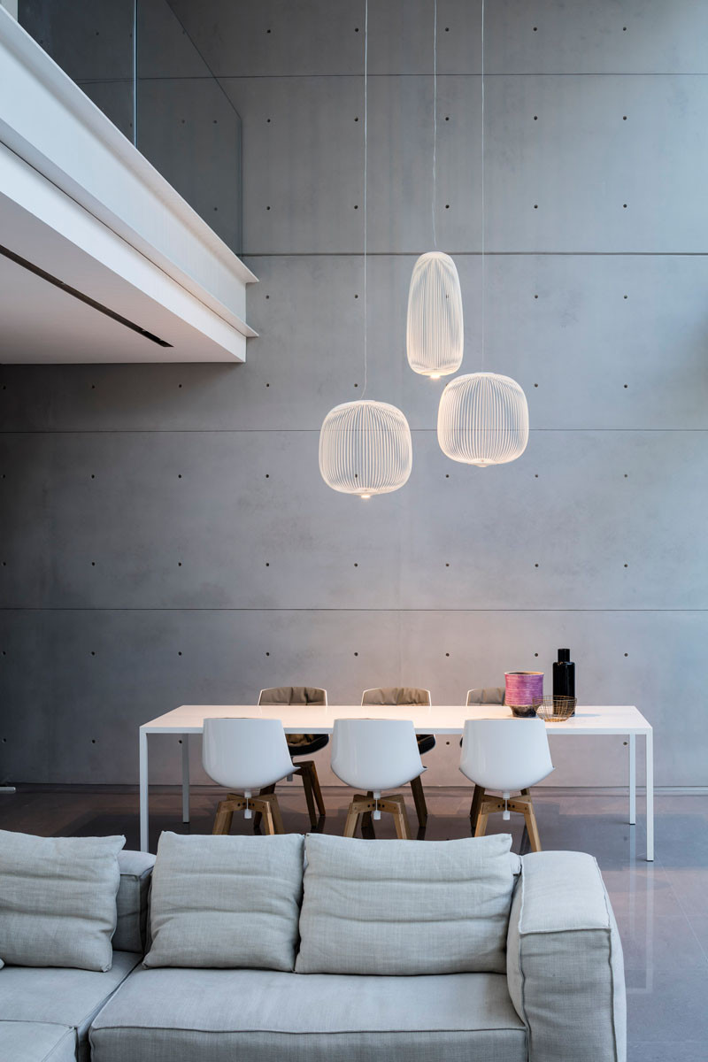 This dining area has three pendant lights that define the location of the table and chairs in this home with an open floor plan.