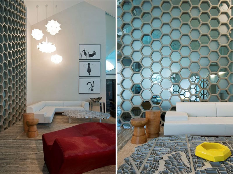 19 Ideas For Using Hexagons In Interior Design And Architecture // This wall of blue glass hexagons separates the living area from the dining area in this family home.