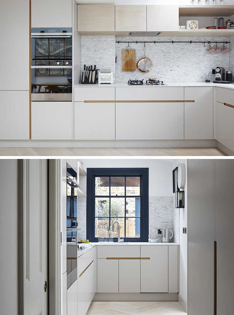 This kitchen has white melamine cabinets with a recessed finger detail made from European oak, to make it easy to open the drawers and cabinets.