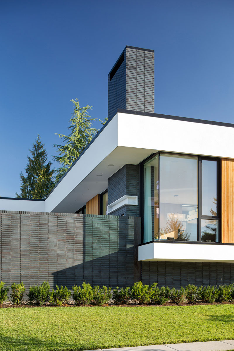 Dark brick contrasts with the white stucco and wood panels.