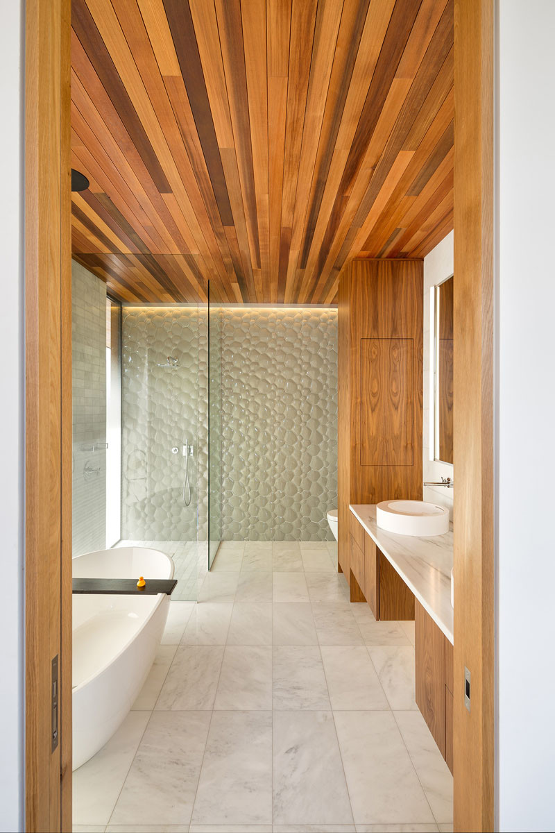 Wood, simple white marble and playful glass tile have been used in the design of this bathroom.