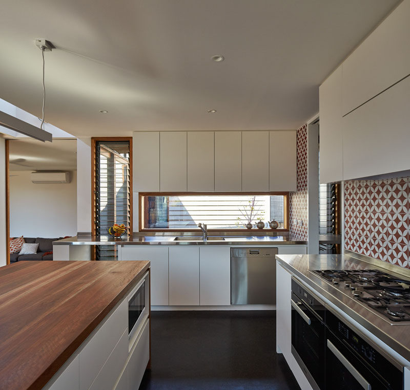 This kitchen has been designed with white cabinets, wood and stainless steel countertops and a red and white patterned backsplash..