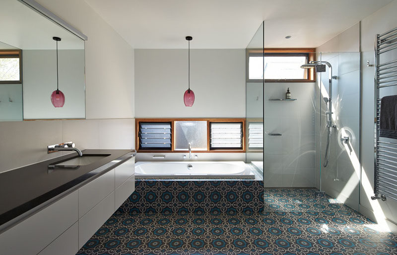 This bathroom has a glass enclosed shower, and tiles that seamlessly flow from the shower to the bathtub surround.