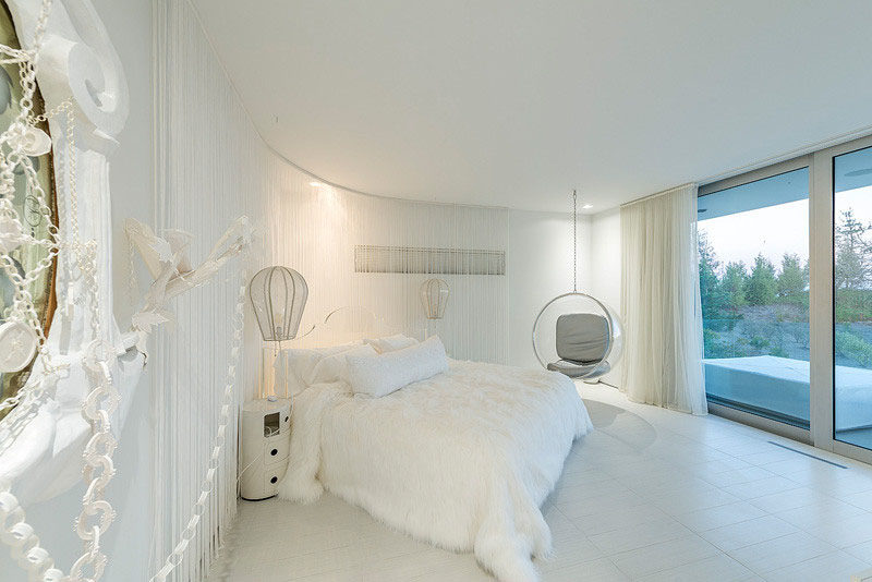 10 Examples Of Monochromatic Interiors // This all white bedroom is whimsical, with a hanging chair, hot-air balloon-shaped lamps, and curtained walls.