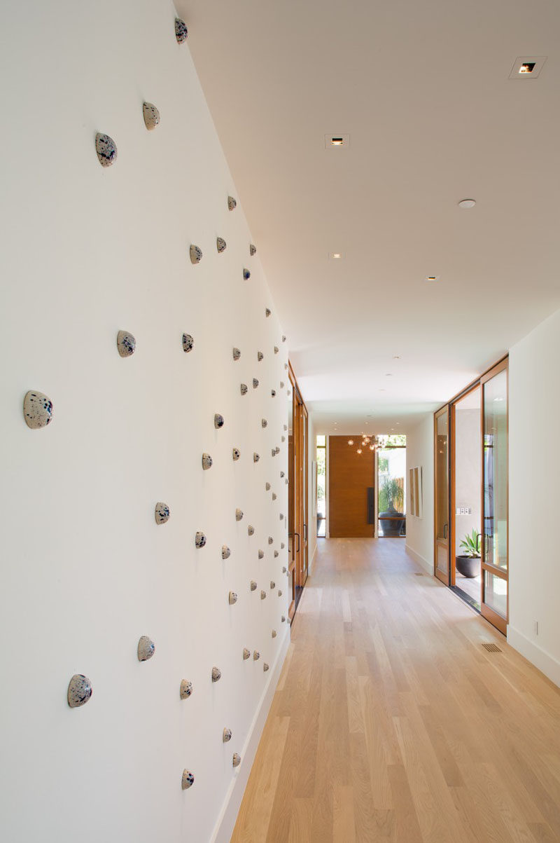 A long white and wood hallway, with artwork to break up the solid white wall.