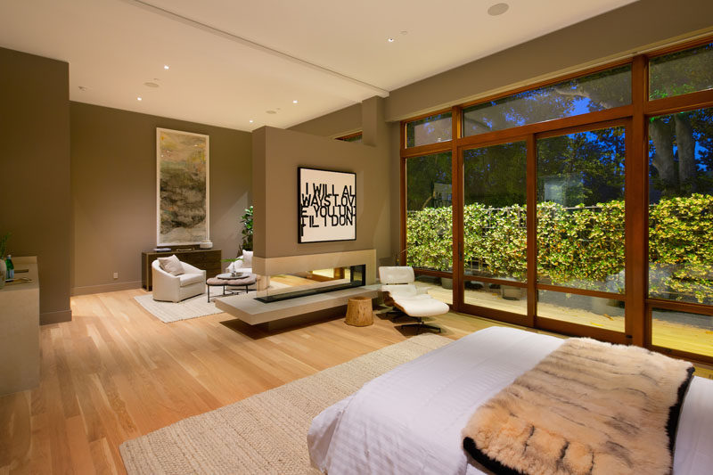 This master bedroom has a private outdoor patio, a see-through fireplace and a small sitting area.