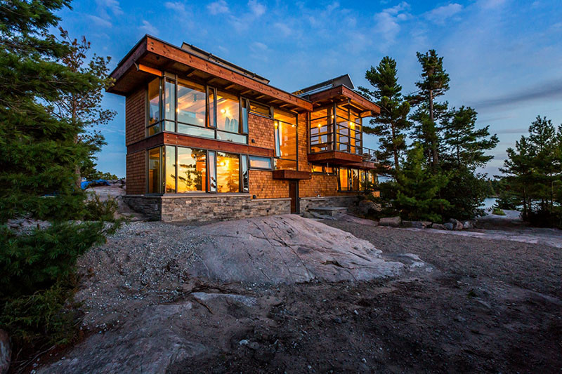 13 Examples Of Modern Houses With Wooden Shingles // This secluded lake house is covered in stone and warm wood shingles.