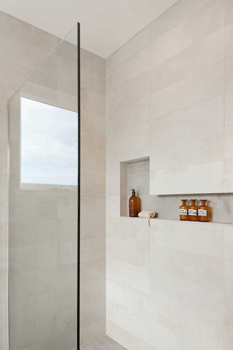 12 Ideas For Including Built-In Shelving In Your Shower // The built-in storage in this shower has varying heights to accommodate taller bottles.
