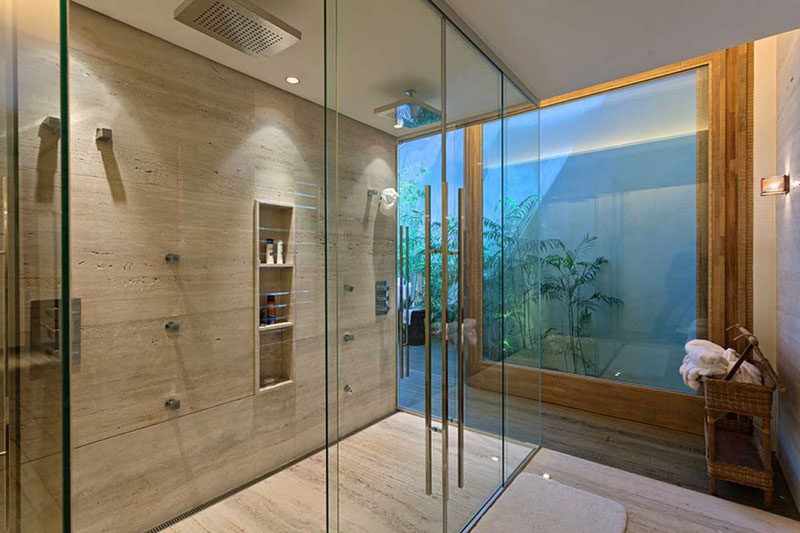 12 Ideas For Including Built-In Shelving In Your Shower // This built-in shelf has three sections, creating enough space for multiple people to store their things in it.
