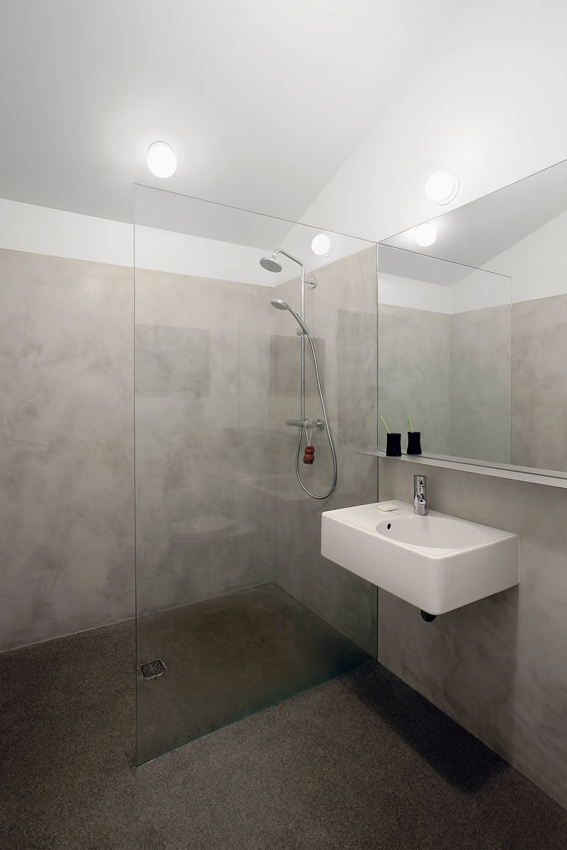 This bathroom has a pitched ceiling, and frame-less glass separates the shower from the rest of the space.