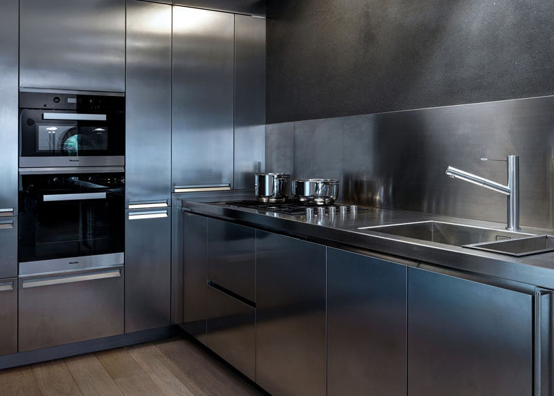 This stainless steel kitchen has appliances, faucet, sink, walls, counter tops, and cabinetry that are all stainless steel to give the kitchen a clean, futuristic look. to maintain the smooth look, hardware has been eliminated in favor of hidden pulls built right into the steel drawers and cabinets.