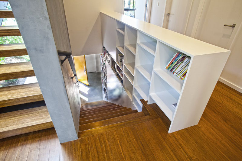 9 Stylish Staircases With Bookshelves As Safety Rails // This Seattle home has a bookshelf running straight up the stairs between the floors.