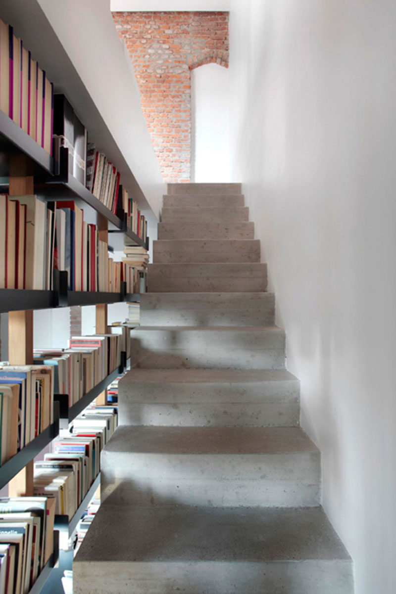 9 Stylish Staircases With Bookshelves As Safety Rails // These concrete stairs are brightened up by the light shining through the open bookshelf.