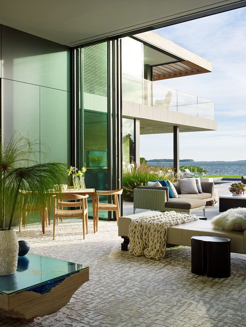 Pops of color have been added to this indoor/outdoor living room, like the blue in the coffee table and the pillow outside.