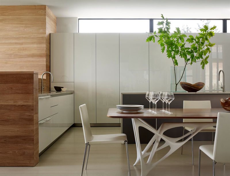 In this kitchen, white cabinets have been paired with wooden touches, like the wall and table top.
