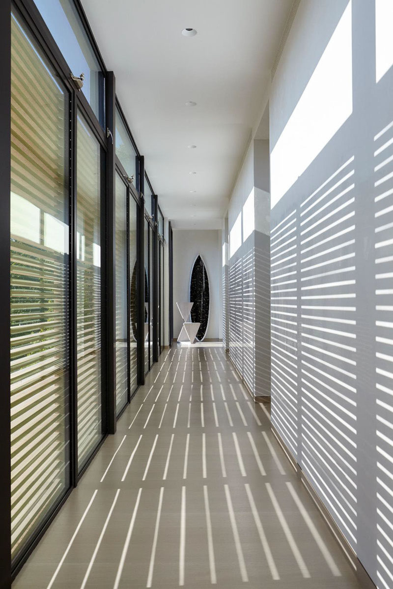 A wall of windows provides light to the hallway, but can also be shaded when needed.