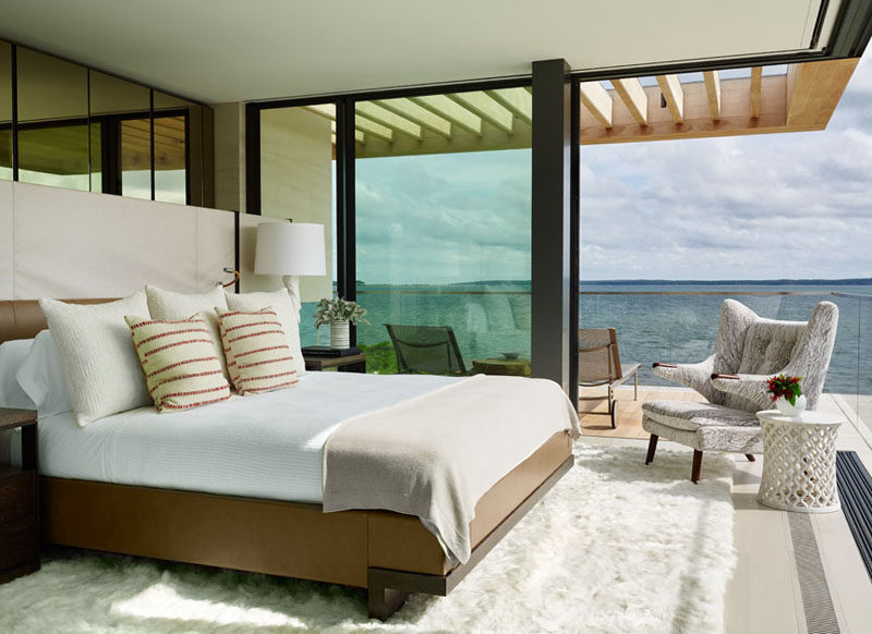 This bedroom opens up to a balcony with lounge chairs and water views.