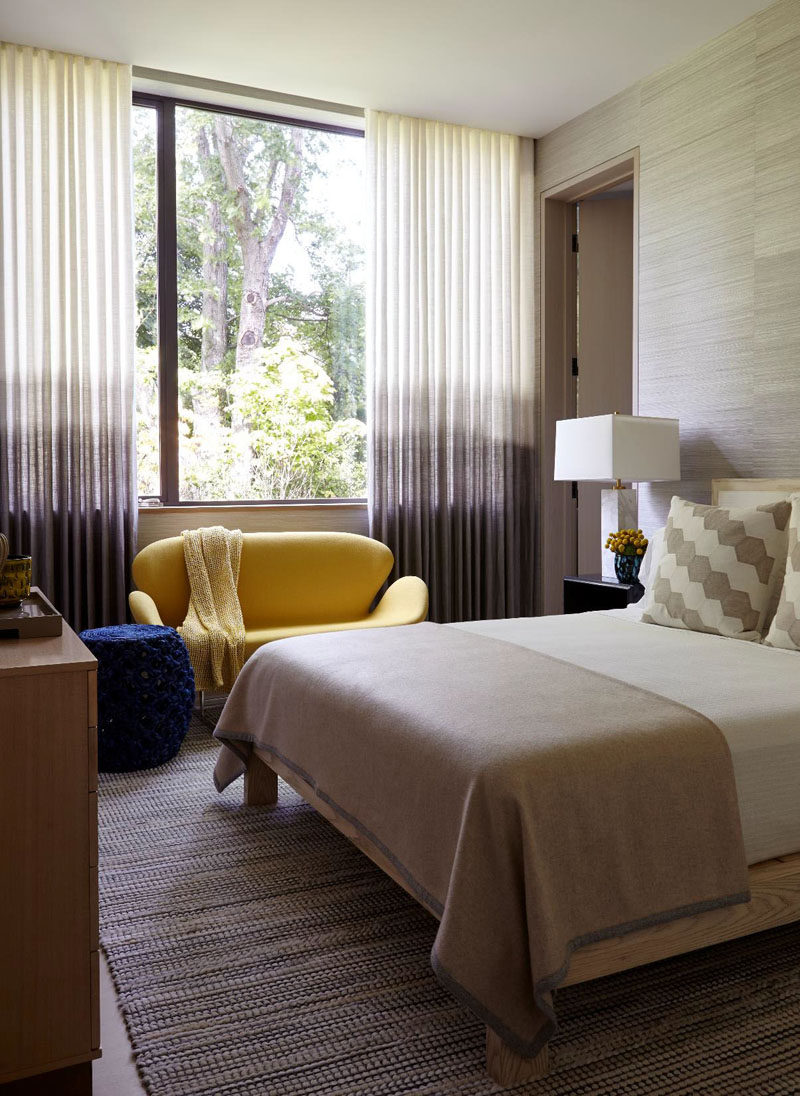 This bedroom has ombré curtains and adds a pop of colour with a small yellow sofa.