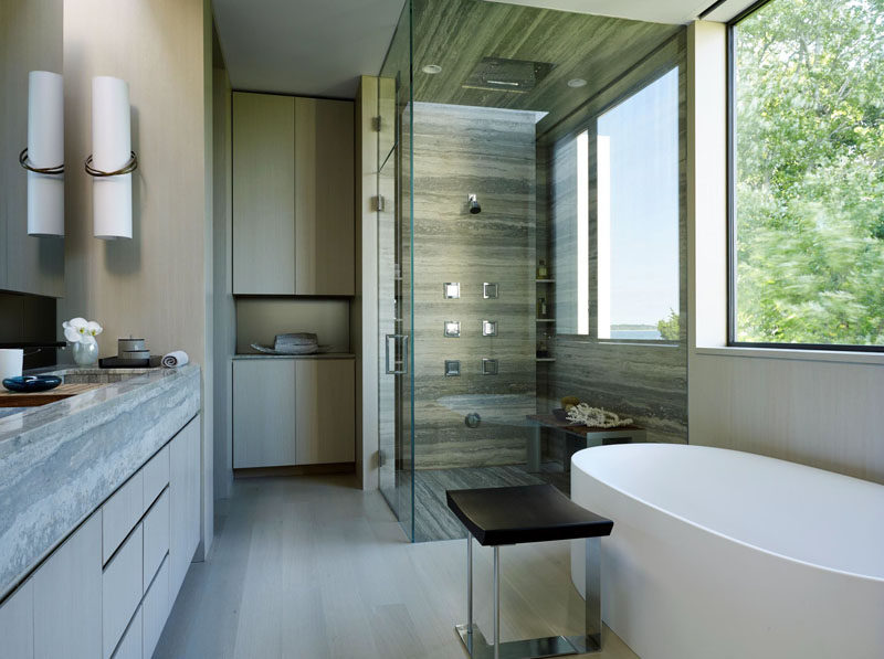 This bathroom has a glass enclosed shower with stone surround, and a large window provides lots of light.