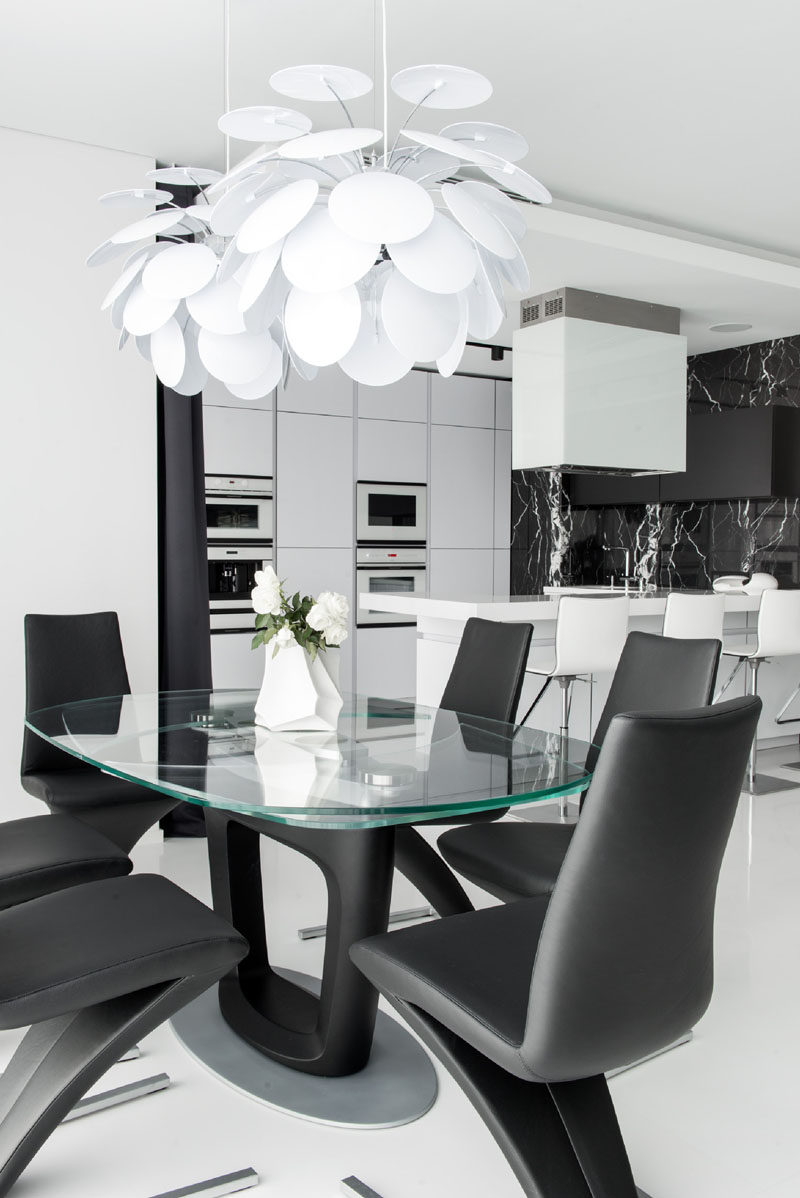 In this black and white home, the dining area has sculptural white pendant lights hanging above a glass top dining table and elegant black chairs.