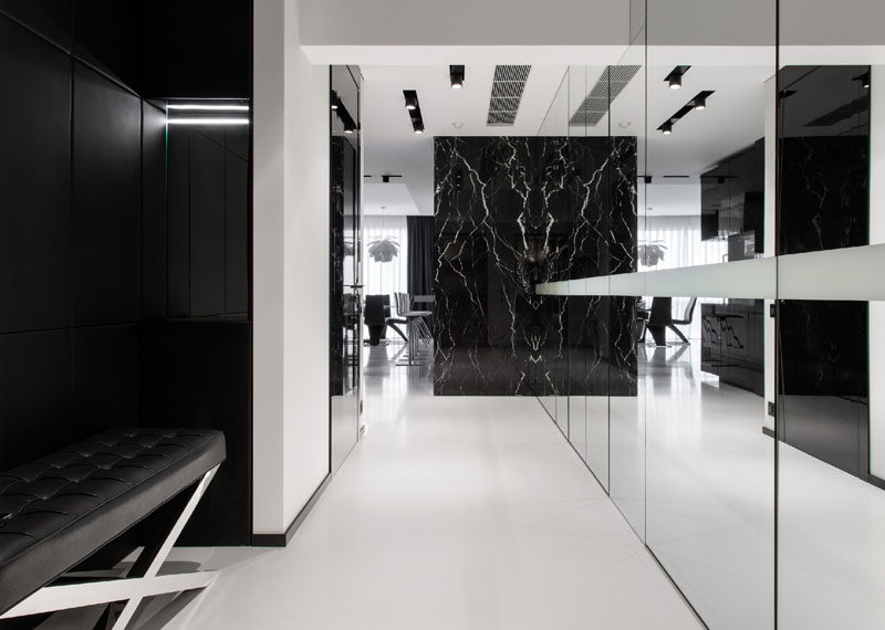 This black and white hallway has a wall of mirrored glass to reflect the light, make the space appear larger and hide additional storage.