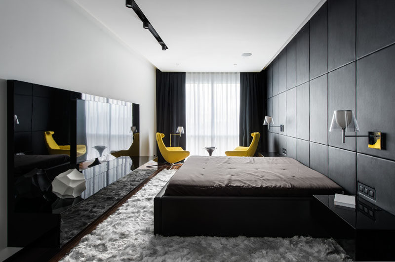 In this black and white bedroom, one wall is entirely covered in custom-designed black leather panels that act as a headboard as well as a decorative feature for the room. A pop of color has been introduced with bright yellow chairs, that have been used draw your eye to the window.