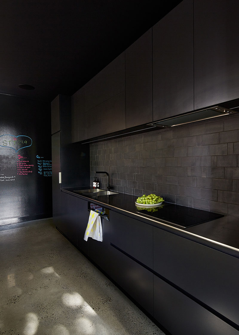 A black backsplash can help create a seamless looking black kitchen. #BlackBacksplash #BlackKitchen #KitchenDesign