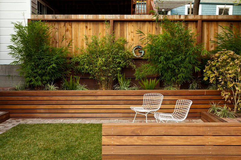 12 Ideas For Including Built-In Wooden Planters In Your Outdoor Space // These wood planters built into the side of the yard match the wood fence surrounding them to make for a cohesive backyard oasis. #WoodPlanters #BuiltInPlanters #Landscaping #LandscapeDesign #BackyardPlanters #YardIdeas