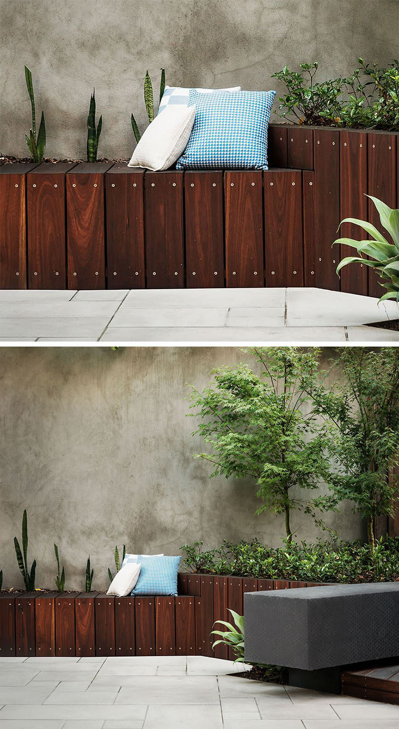12 Ideas For Including Built-In Wooden Planters In Your Outdoor Space // The contrast between the dark wood and the concrete wall add style and functionality to the back yard in the form of seating and planters. #WoodPlanters #BuiltInPlanters #Landscaping #LandscapeDesign #BackyardPlanters #YardIdeas