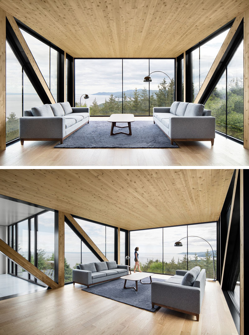 This living room with light wood details, cantilevers out away from the house, providing it with an amazing view from the floor-to-ceiling windows.