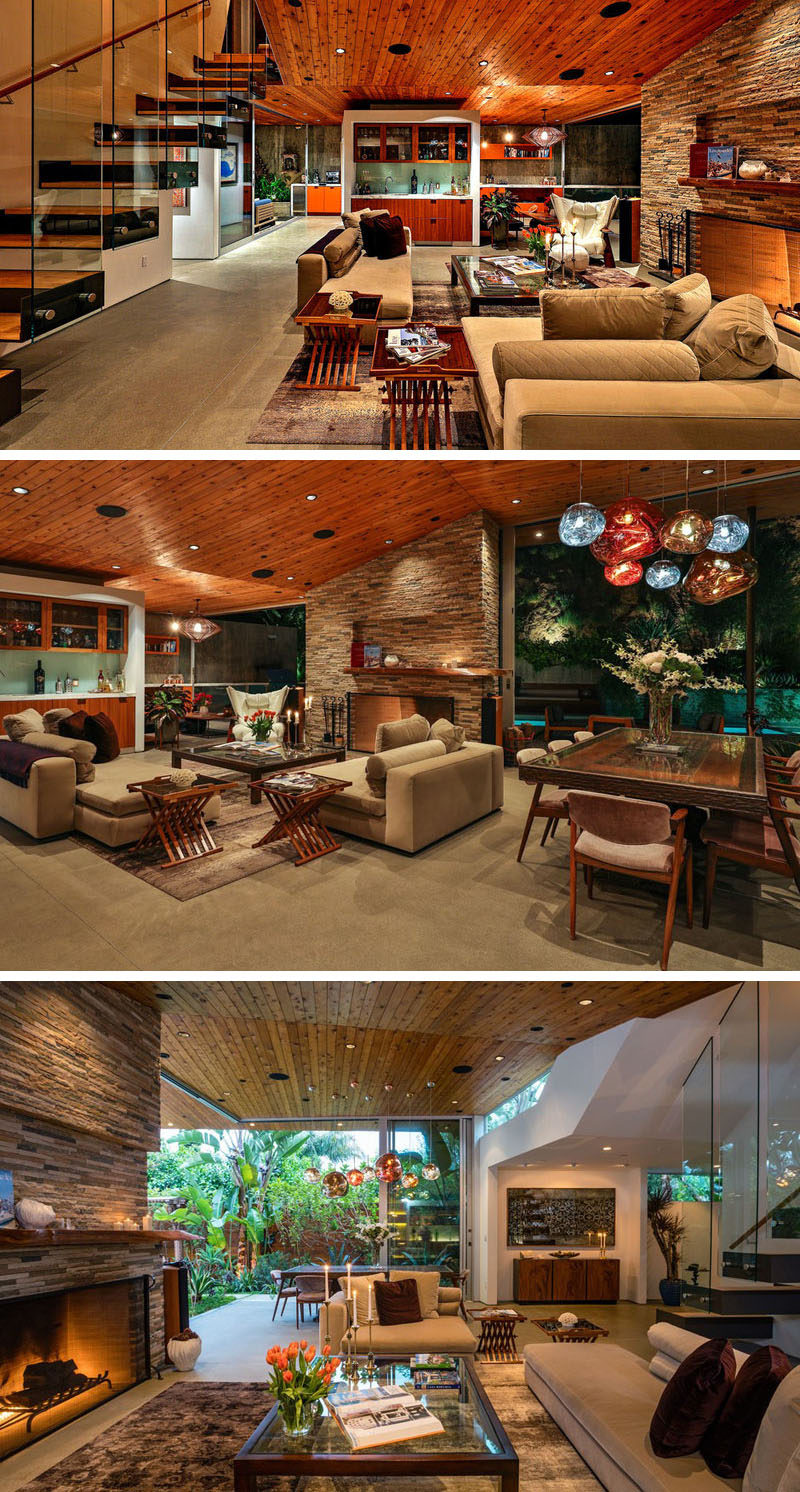 This home, designed by SPACE International, has a large living room that shares the space with the dining area. The wooden ceiling flows from the outside of the home to the interior, joining the two two areas to create a single cohesive look.