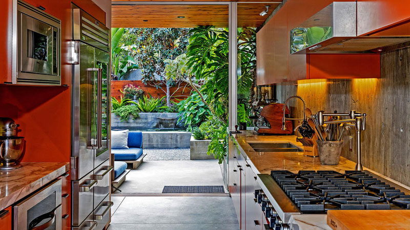 This kitchen with stainless steel appliances, opens up to a small patio area.