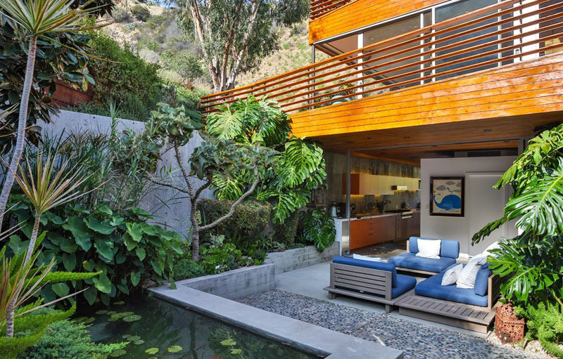 This private patio, located off the home's kitchen, has comfortable lounges for relaxing and a koi pond.