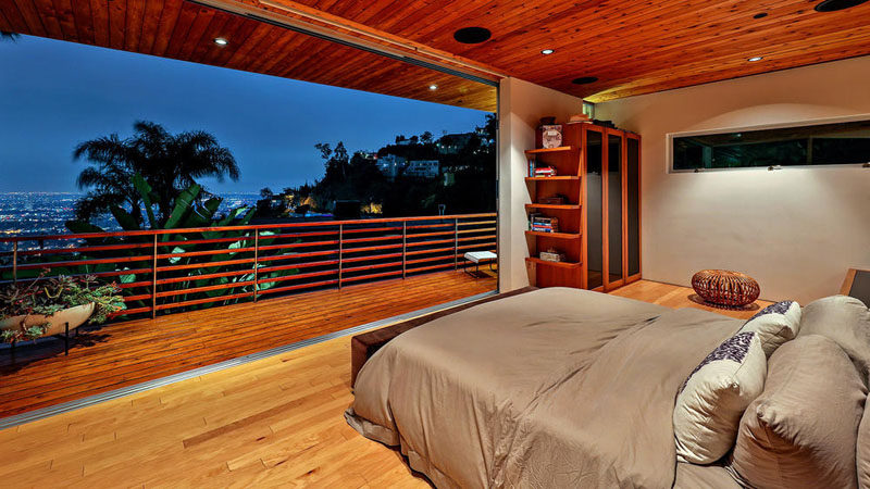 This bedroom has a wall that opens up to a private balcony with views of Hollywood.